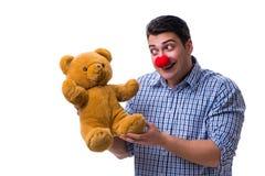 Hombre divertido del payaso con un juguete suave del oso de peluche aislado en el CCB blanco foto de archivo libre de regalías