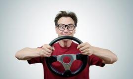 Hombre divertido en los vidrios con un volante, concepto de la impulsión del coche Imagenes de archivo