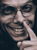 Hombre divertido en los vidrios que escogen su nariz Imágenes de archivo libres de regalías