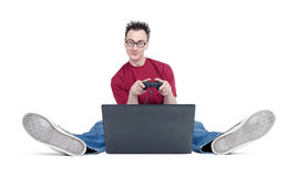 Hombre divertido en los vidrios redondos, sentándose en el piso y jugando a juegos en el ordenador portátil En el fondo blanco Fotografía de archivo