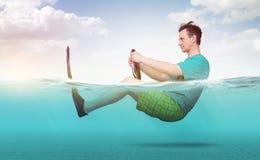 Hombre divertido en pantalones cortos, camiseta y paseos de las aletas en el mar con un volante del coche Concepto de ir el vacac foto de archivo