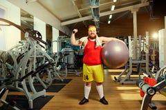 Hombre divertido gordo en el gimnasio imagenes de archivo