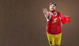 Hombre divertido gordo en un traje del super héroe Foto de archivo libre de regalías