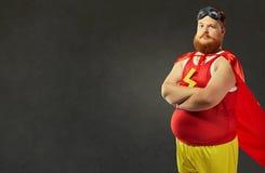Hombre divertido gordo en un traje del super héroe Imagen de archivo