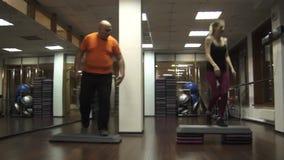 Hombre divertido gordo que intenta hacer pasos cerca de mujer joven hermosa joven del deporte