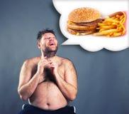 Hombre divertido gordo que sueña sobre la hamburguesa imagen de archivo libre de regalías