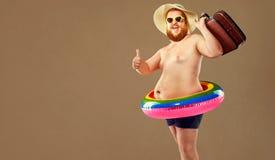 Hombre divertido grueso en los troncos de natación que llevan un sombrero y un o hecho a ganchillo imagen de archivo