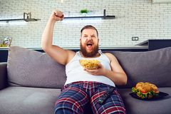 Hombre divertido grueso en pijamas que come una hamburguesa que se sienta en el sofá fotografía de archivo libre de regalías