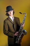 hombre divertido joven en saxofón de la explotación agrícola del hongo Foto de archivo libre de regalías