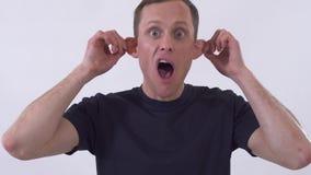 Hombre divertido loco joven hacer caras extrañas Tiroteo en un fondo blanco almacen de video