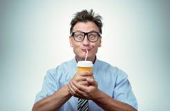 Hombre divertido que bebe de una taza de papel con una paja fotos de archivo