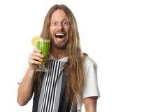 Hombre divertido que bebe el smoothie vegetal verde Foto de archivo