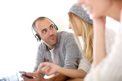 Hombre divertido que escucha la música con los amigos Imagen de archivo