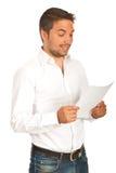 Hombre divertido que lee un papel Fotos de archivo