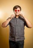 Hombre divertido que lleva a cabo corazones rojos delante de ojos Imagen de archivo
