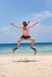 Hombre divertido que salta en aletas y máscara imagen de archivo