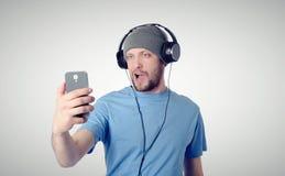 Hombre divertido que se fotografía en un smartphone Imágenes de archivo libres de regalías
