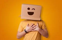 Hombre divertido que sonríe con la cabeza de la caja de cartón imagen de archivo libre de regalías