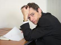 Hombre doloroso en la oficina, en un lugar de trabajo Imagen de archivo