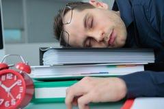 Hombre dormido en carpetas de la pila fotografía de archivo libre de regalías