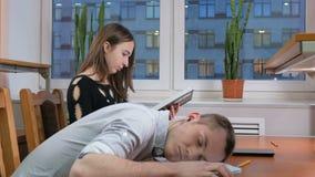 Hombre durmiente del estudiante cansado con los auriculares en una conferencia en el cuaderno Cerca de la mujer de los expediente almacen de metraje de vídeo
