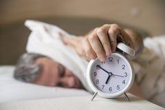 Hombre durmiente molestado por madrugada del despertador Oídos soñolientos de la cubierta del hombre con la almohada fotografía de archivo libre de regalías