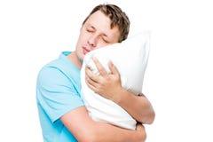 Hombre durmiente que abraza la almohada suave contra blanco Foto de archivo