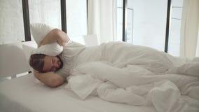 Hombre durmiente que despierta por mañana del ruido afuera almacen de video