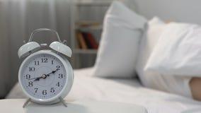 Hombre durmiente que despierta sano de la alarma molesta en la cama, privación del resto, recordatorio metrajes
