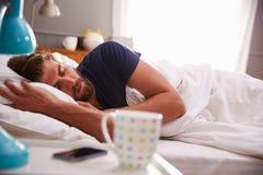 Hombre durmiente que es despertado por el teléfono móvil en dormitorio fotos de archivo