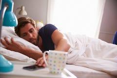 Hombre durmiente que es despertado por el teléfono móvil en dormitorio fotos de archivo libres de regalías