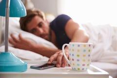 Hombre durmiente que es despertado por el teléfono móvil en dormitorio foto de archivo