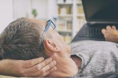 Hombre duro de oído que usa el ordenador portátil Foto de archivo
