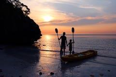 Hombre e hija kayaking en la playa Imagen de archivo libre de regalías
