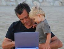 Hombre e hijo con el ordenador imagen de archivo libre de regalías