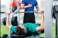 Hombre e instructor personal en gimnasio Imagen de archivo