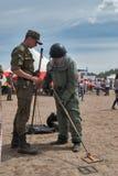 Hombre - el visitante de la demostración intenta encendido el traje del bombero Imagen de archivo