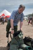 Hombre - el visitante de la demostración intenta encendido el traje del bombero Foto de archivo libre de regalías