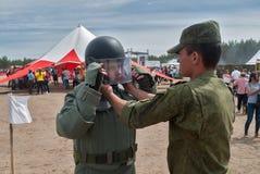 Hombre - el visitante de la demostración intenta encendido el traje del bombero Foto de archivo
