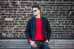 Hombre elegante adulto joven de moda que presenta el pulower rojo al aire libre que lleva, vaqueros, la chaqueta del algodón y la Foto de archivo libre de regalías