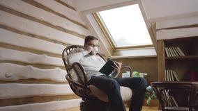Hombre elegante barbudo en vidrios que lee un libro y que bebe el café en el ático almacen de video