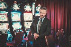 Hombre elegante cerca de las máquinas de ranuras en un interior de lujo del casino fotografía de archivo