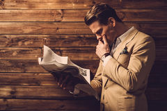 Hombre elegante con el periódico en interior rural de la cabaña Fotografía de archivo libre de regalías