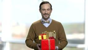 Hombre elegante con las cajas de regalo en fondo borroso almacen de metraje de vídeo