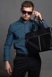 Hombre elegante con un bolso y las gafas de sol foto de archivo