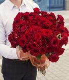 hombre elegante con un ramo de rosas rojas Foto de archivo