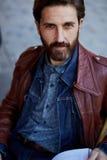 Hombre elegante con una barba que sostiene una revista Fotografía de archivo