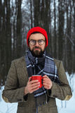 Hombre elegante de la barba con una bebida caliente en la taza roja en un invierno delantero Fotografía de archivo libre de regalías