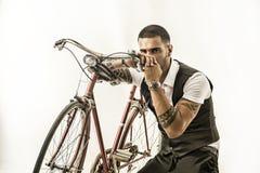 Hombre elegante de Tattoed que completa un ciclo en la bicicleta Imágenes de archivo libres de regalías