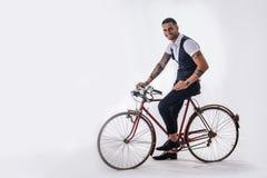 Hombre elegante de Tattoed que completa un ciclo en la bicicleta Imagen de archivo libre de regalías